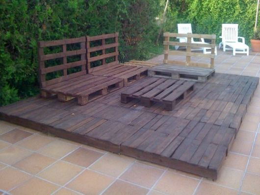 Foto de um deck de pallets com bancos de madeira sobre ele