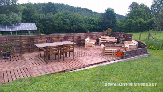 Deck de pallets muito grandes com duas mesas e diversas cadeiras, todas feitas de madeira também