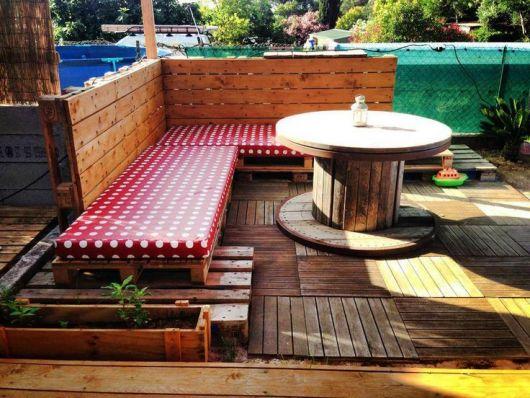 Três Decks de pallets sobrepostos em um chão repleto de pedras com um pequeno jardim ao fundo