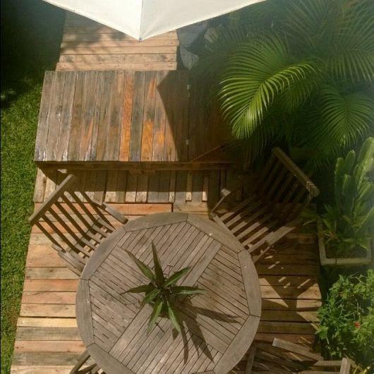Foto tirada de cima de um deck de pallets, com uma mesa de madeira e um banco ao lado dela
