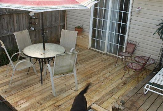 Foto de um deck de pallets com uma mesa de centro na área externa de uma casa