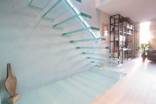 Escada flutuante de vidro em um ambiente claro e muito iluminado