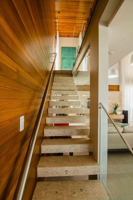 Escada flutuante feita de concreto com um corrimão nas lateral apoiada em uma parede madeira