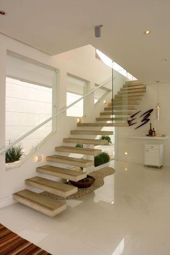 Escada flutuante feita de concreto em uma casa toda pintada de branco
