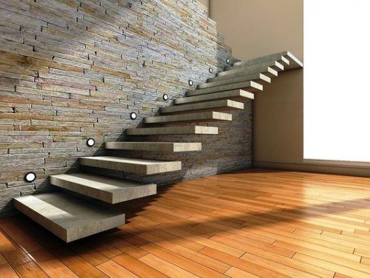 Escada flutuante feita de concreto apoiada em uma parede de pedra