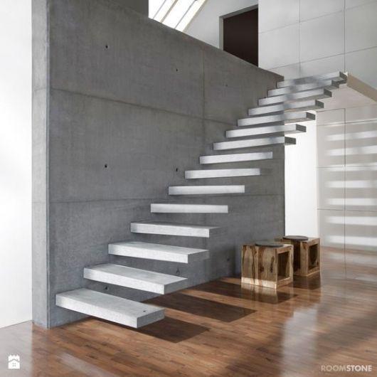 Escada flutuante feita de concreto apoiada em uma parede cinza acima de um piso de madeira