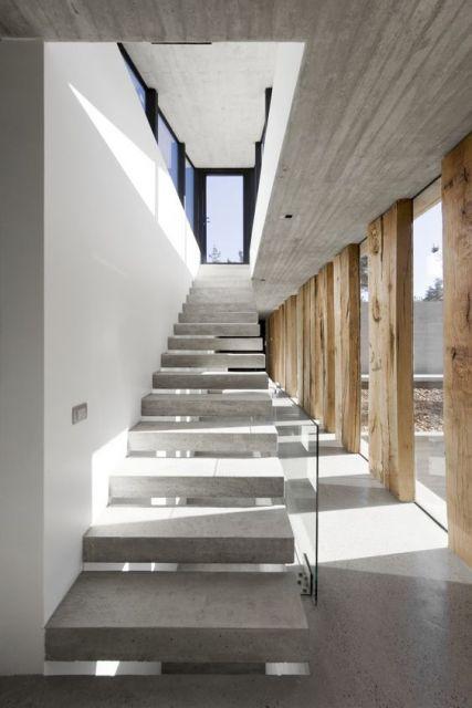Escada flutuante feita de concreto em um corredor muito iluminado