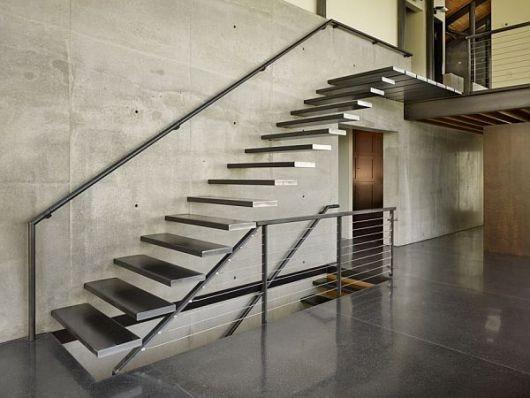 Escada flutuante feita de ferro em um ambiente todo pintado de cinza