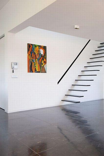 Escada flutuante de ferro com um corrimão na lateral próximo de um quadro e apoiada em uma parede branca