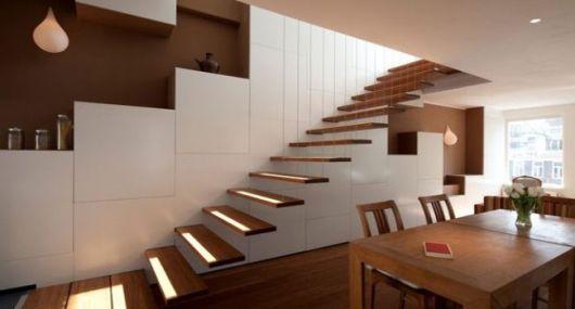 Escada flutuante feita de madeira apoiada em uma parede branca e próximo em uma mesa e cadeiras de madeira