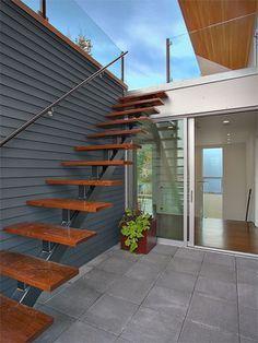 Escada flutuante de madeira em um jardim apoiada em uma parede cinza