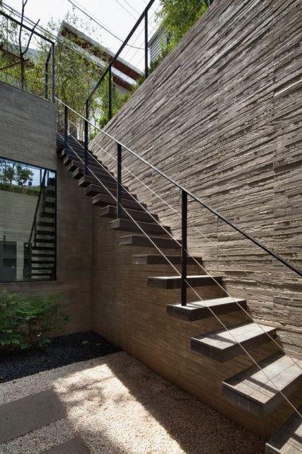 Escada flutuante muito alta que vai até um jardim com um corrimão em sua lateral