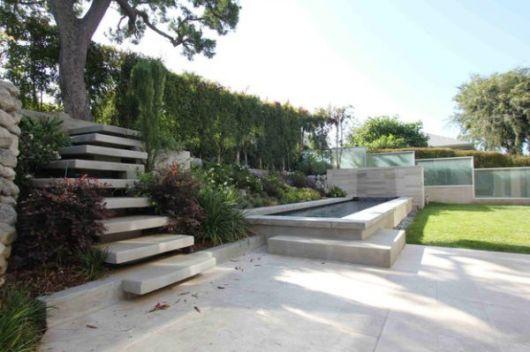 Escada flutuante de concreto em um jardim com muita água e vegetação