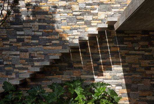 Escada flutuante de concreto acima de algumas plantas e apoiada em uma parede feita de pedras