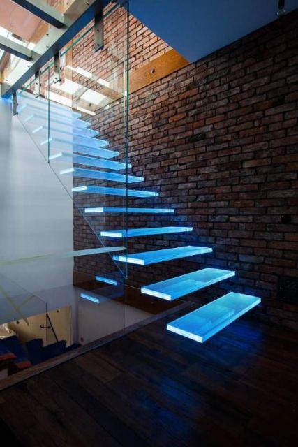 Escada flutuante apoiada em uma parede com tijolos a mostra e iluminação muito forte