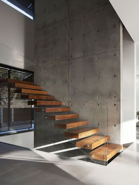 Escada flutuante de madeira com degraus grossos apoiada em uma parede muito alta