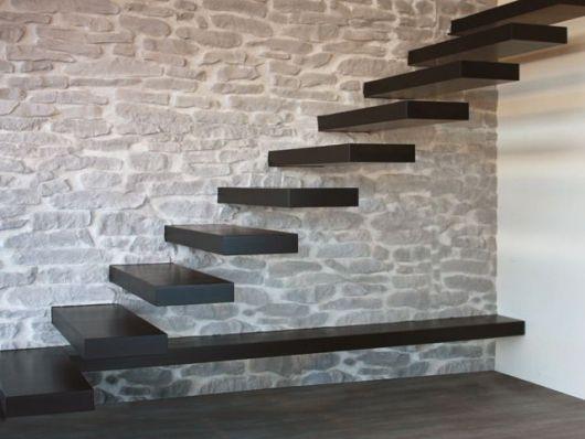 Escada flutuante preta apoiada em uma parede feita de pedras
