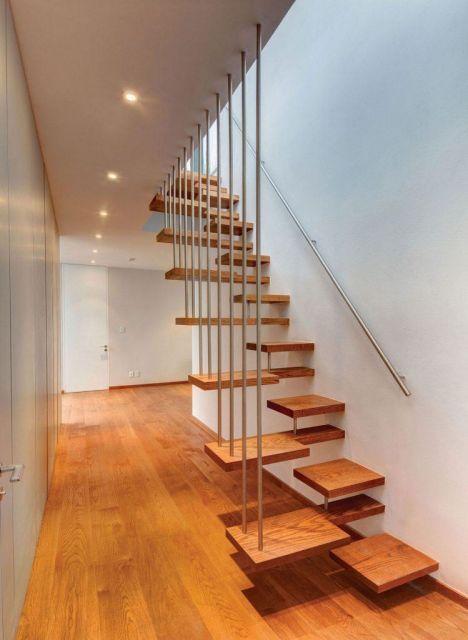 Escada flutuante de madeira com degraus personalizados e barras de proteção em sua lateral