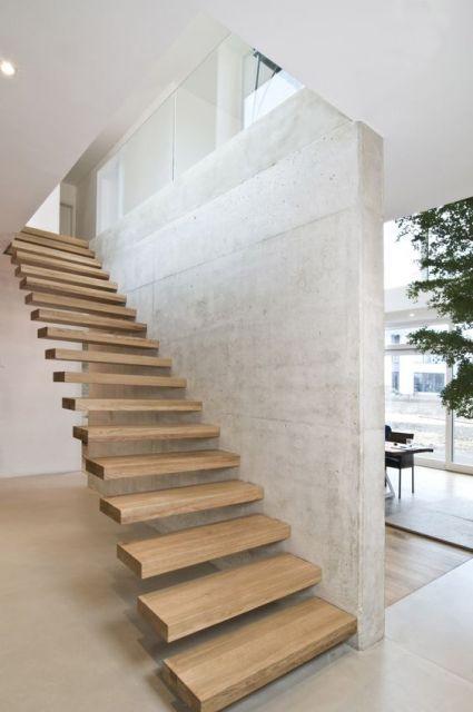 Escada flutuante feita de madeira com degraus grossos apoiada em uma parede branca