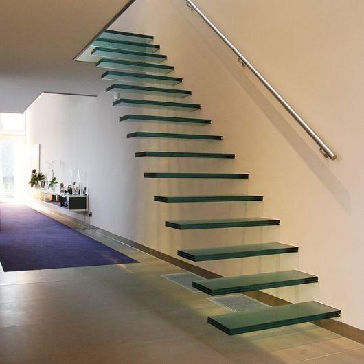 Escada flutuante de vidro com um apoiada em uma parede branca