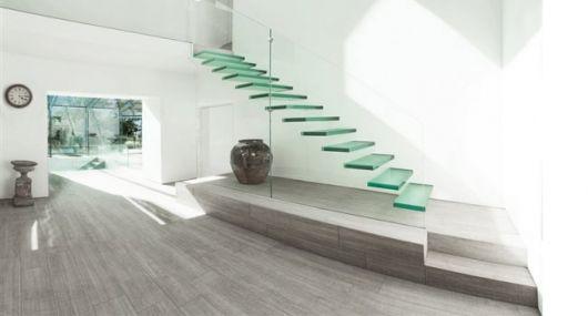 Escada flutuante de vidro em um cômodo todo pintado de branco próxima a uma relógio e um vaso