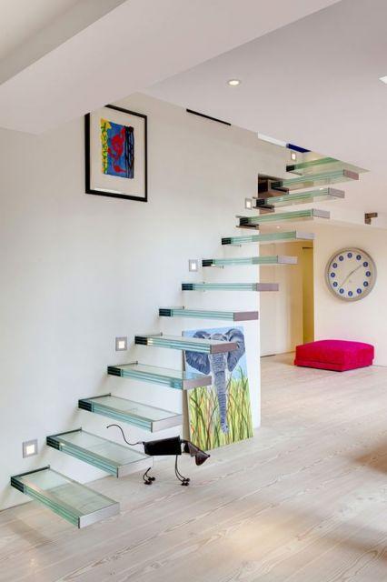 Escada flutuante de vidro em uma sala enfeitada com um sofá rosa, dois quadros colorido e um relógio