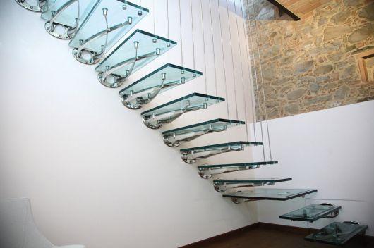 Foto tirada de baixo para cima de uma escada flutuante feita de vidro, apoiada em uma parede branca