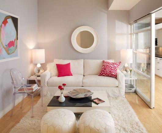 sala pequena com sofá e puff