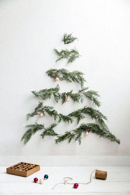 árvore de Natal suspensa com folhas de pinheiro na parede