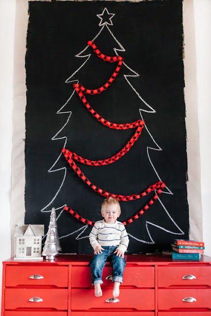 árvore de Natal suspensa desenhada com giz sobre um móvel vermelho