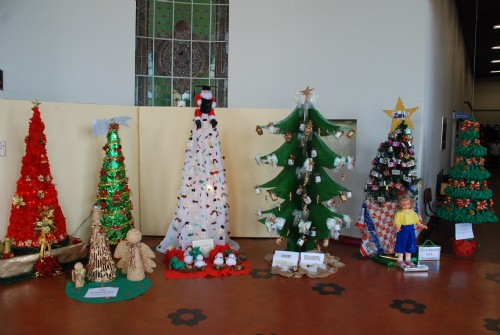 árvores de Natal de diferentes estilos em corredor de escola