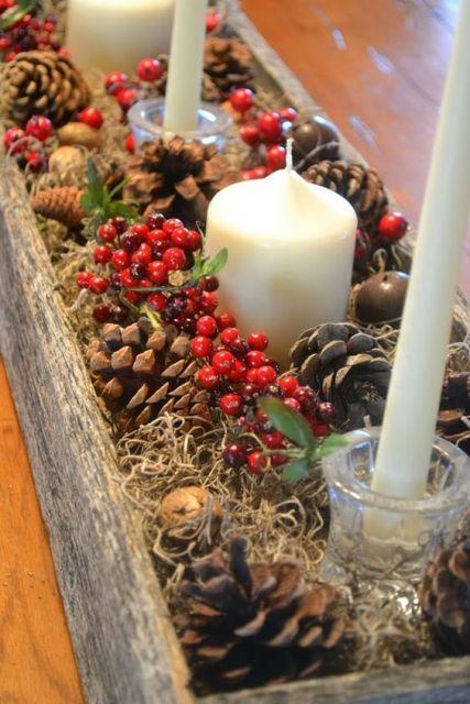 Caixote com pinhas, velas e frutas artificiais.