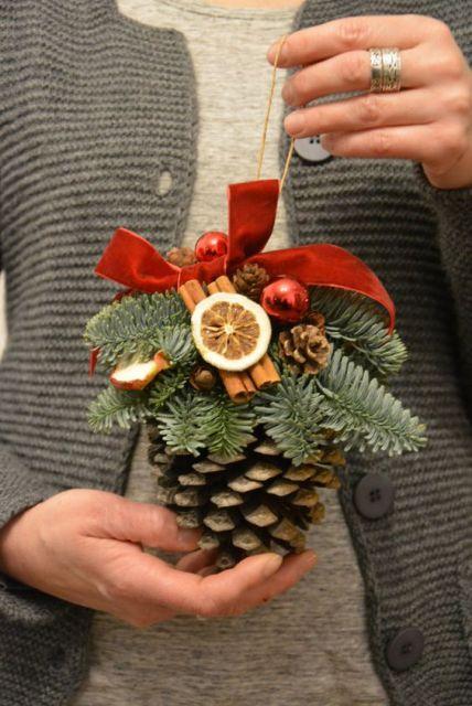 Enfeite de pinha, feito com laço e outros itens decorativos.