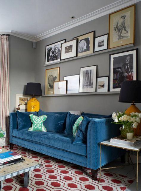 Sofá azul petróleo com quadros na parede de trás.