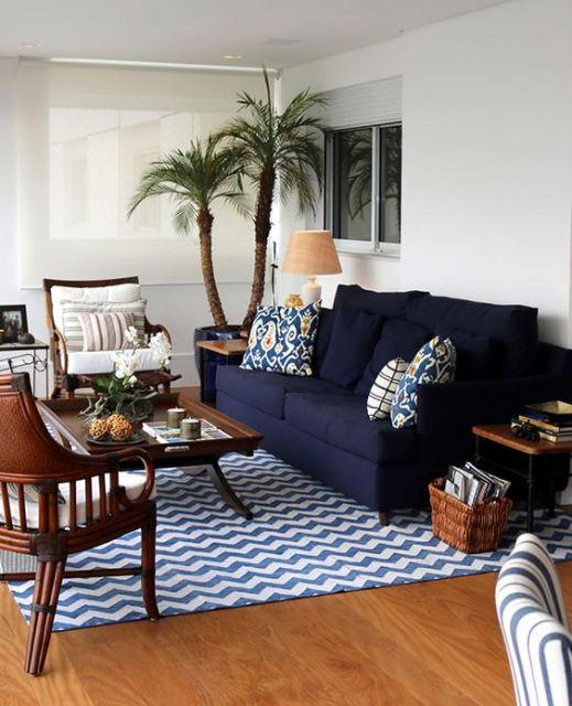 Sofá azul de dois lugares, combinado com poltronas de madeira.