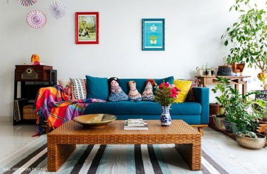 Sofá azul em sala de estar, com almofadas coloridas.