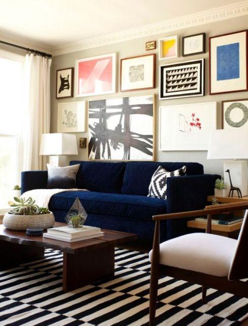 Parede com diversos quadros, com sofá azul encostado.