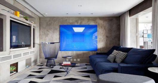 Sala com piso geométrico e sofa azul.