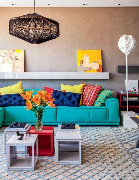 Sofá tiffany com almofadas azuis, vermelhas, amarelas e verdes.
