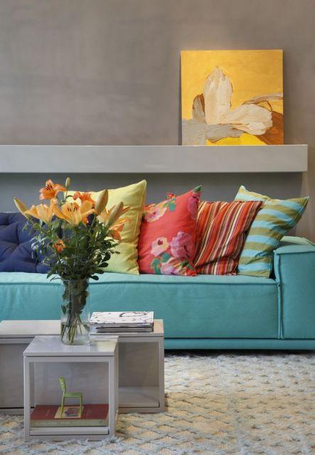 Sala com paredes neutras e almofadas coloridas.