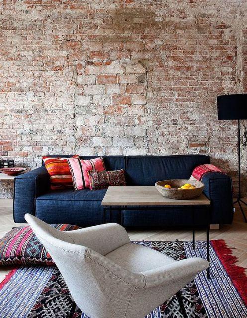 Sofá de dois lugares espaçoso, em frente a parede de tijolos.