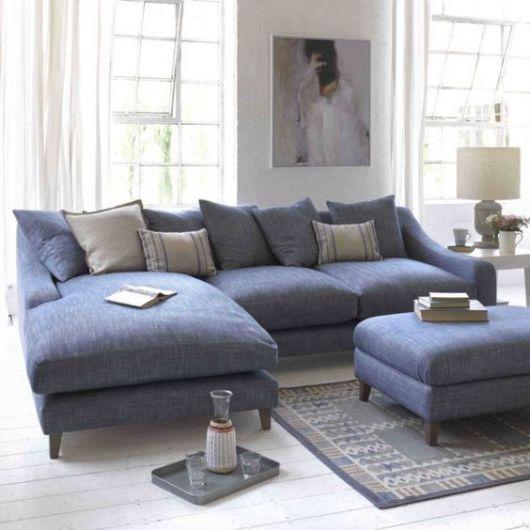 Sofá de canto azul, com almofadas claras.