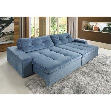 Sala com paredes de madeira, piso claro e sofá azul.
