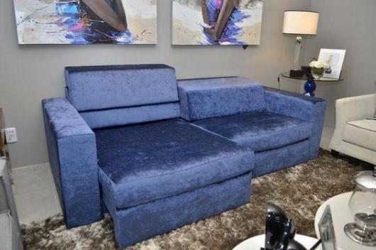 Sala com sofá azul retrátil, tapete marrom e quadros.