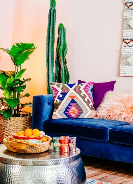 Sofá azul royal em sala de estar, com almofadas coloridas.