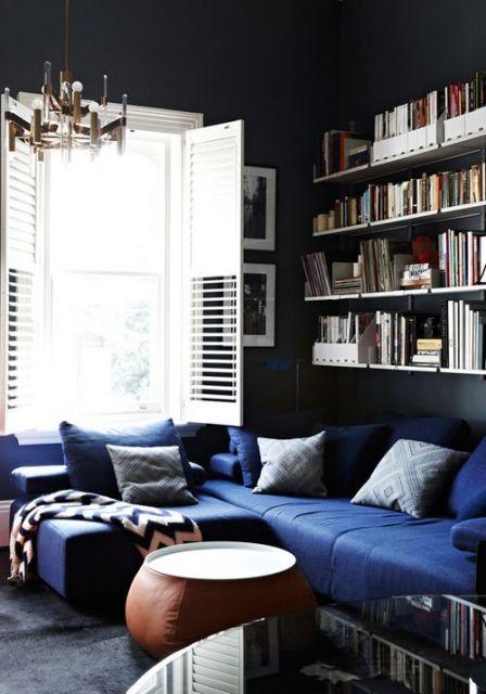 Cômodo com sofá de canto e prateleiras de livros.