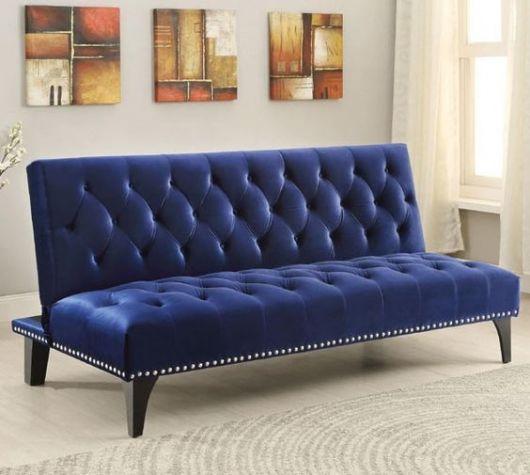 Sofá azul royal encostado em parede neutra com quadros.