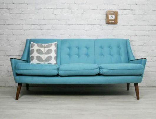 Sofá azul claro de três lugares com parede de tijolos clara.