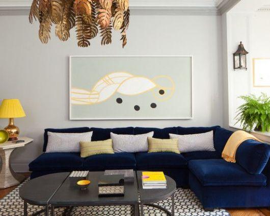Sofá de canto azul escuro, com almofadas amarelas.