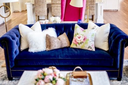 Sofá azul royal com almofadas claras.